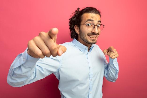 카메라를보고 웃고 진홍색 배경에 고립 제스처를하고있는 안경을 쓰고 감동 젊은 잘 생긴 백인 남자