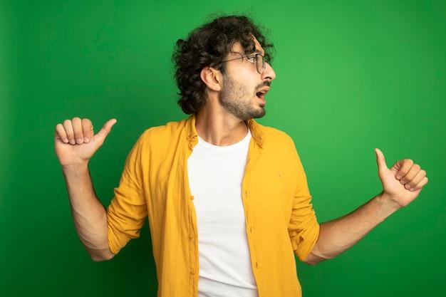緑の背景に分離された側を見て自分自身を指している眼鏡をかけている感動の若いハンサムな白人男性