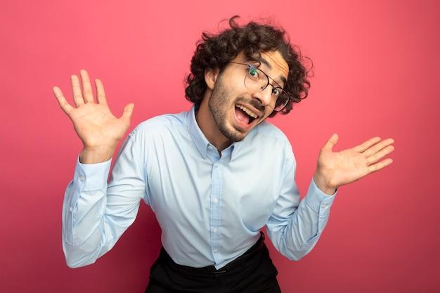 真っ赤な背景に分離されたカメラを見て空の手を示す眼鏡をかけている感動の若いハンサムな白人男性