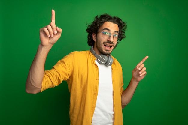 印象的な若いハンサムな白人男性は、緑の壁に隔離された上向きのヘッドフォンで眼鏡をかけています