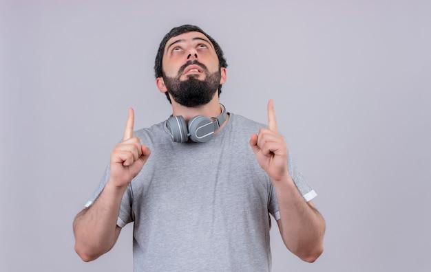 Impressionato giovane uomo caucasico bello che indossa le cuffie sul collo alla ricerca e rivolto verso l'alto isolato su bianco con lo spazio della copia