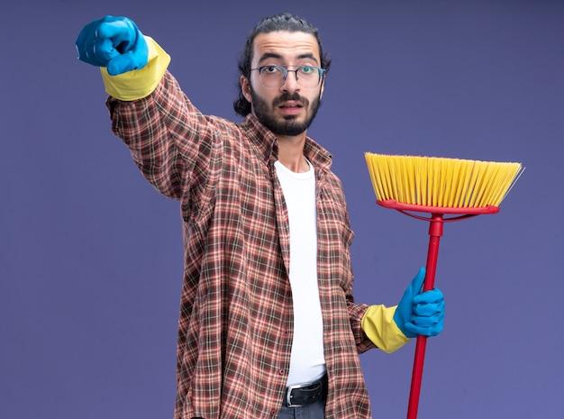 Впечатленный молодой красивый уборщик в футболке и перчатках держит швабру, показывая вам жест, изолированный на синей стене