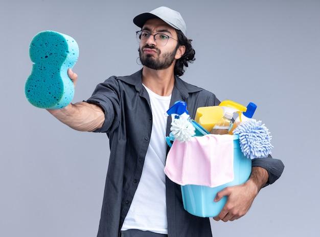 Impressionato giovane bel ragazzo delle pulizie che indossa t-shirt e berretto che tiene secchio di strumenti per la pulizia e guardando la spugna in mano isolata sul muro bianco