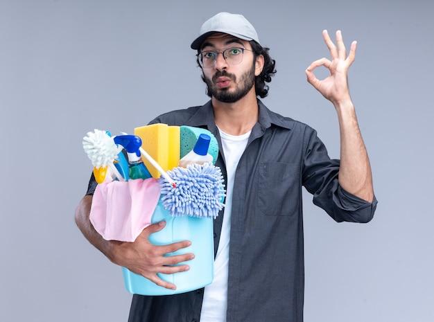 Giovane ragazzo bello delle pulizie impressionato che indossa la maglietta e il berretto che tengono il secchio degli strumenti di pulizia che mostrano il gesto giusto isolato sulla parete bianca