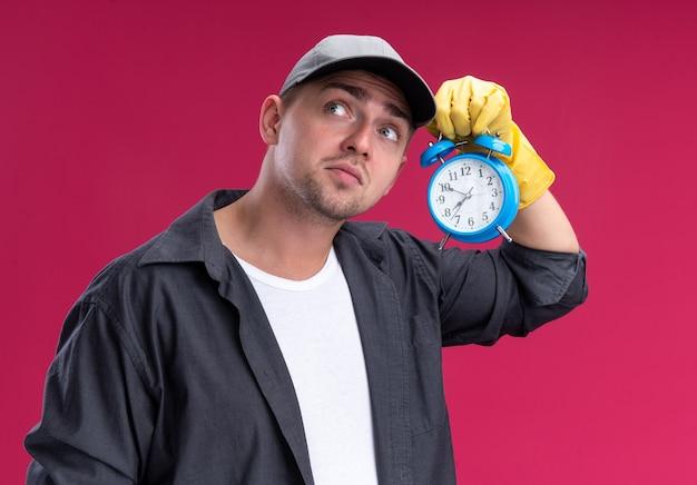 Impressionato giovane bel ragazzo delle pulizie che indossa t-shirt e berretto con i guanti che tengono e ascolta la sveglia isolata sulla parete rosa