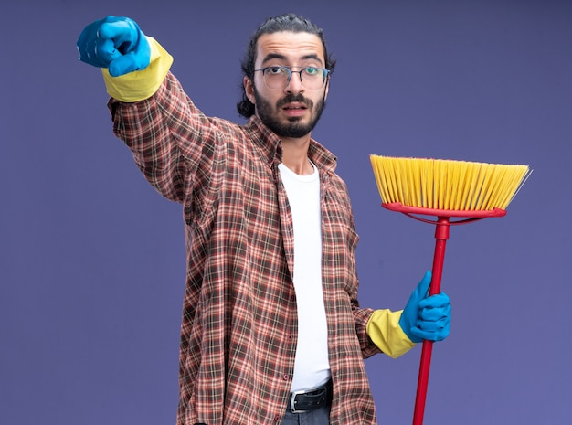 Impressed young handsome cleaning guy wearing t-shirt and gloves holding mop showing you gesture isolated on blue wall