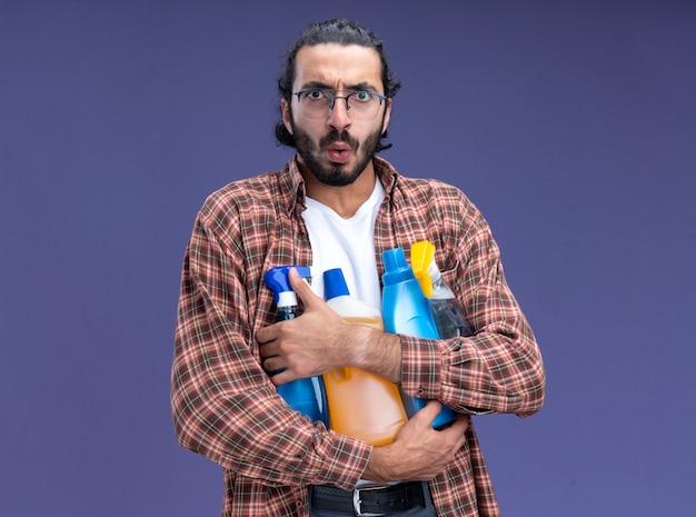 青い壁に分離されたクリーニングツールを保持しているtシャツを着ている感動の若いハンサムなクリーニング男
