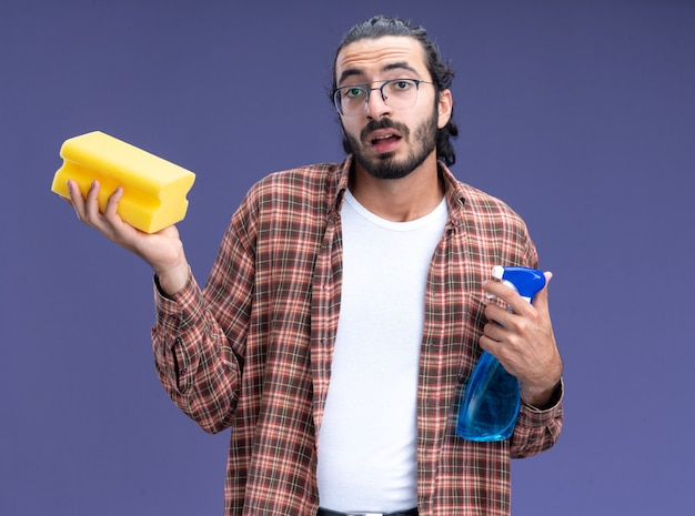 Impressed young handsome cleaning guy wearing t-shirt holding spray bottle with sponge isolated on blue wall