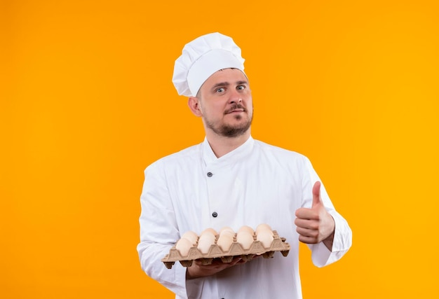 Impressed young handsome cook in chef uniform holding carton of eggs showing thumb up isolated on orange wall