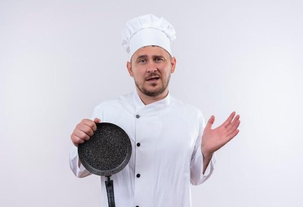 Impressionato giovane e bello cuoco in uniforme da chef che tiene in mano una padella che mostra la mano vuota isolata sul muro bianco