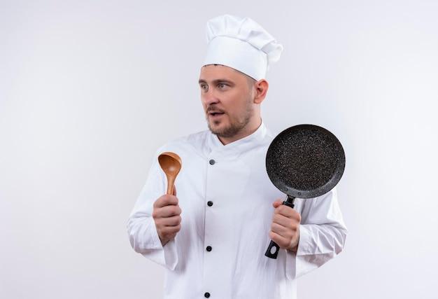 Impressionato giovane e bello cuoco in uniforme da chef che tiene padella e cucchiaio guardando il lato isolato sul muro bianco