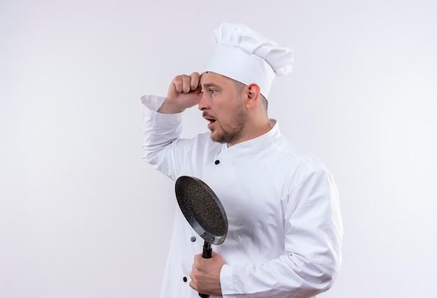 Impressionato giovane bel cuoco in uniforme da chef che tiene padella in piedi in vista di profilo guardando il lato con la mano sulla testa isolata sul muro bianco