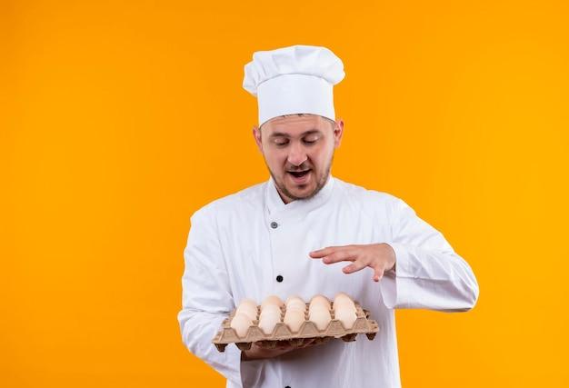 Impressionato giovane e bello cuoco in uniforme da chef che tiene e guarda il cartone di uova tenendo la mano sopra di esso isolata sul muro arancione