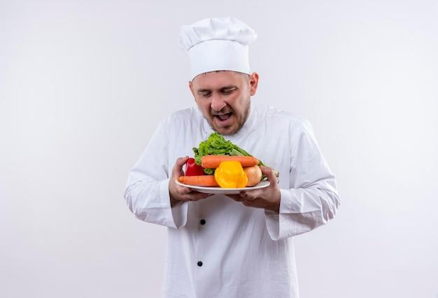 Impressionato giovane bel cuoco in uniforme da chef che tiene piatto con verdure che li guardano sul muro bianco isolato isolated