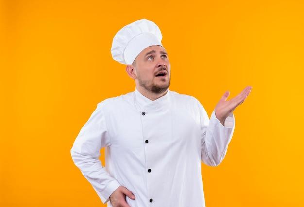 Impressionato giovane bel cuoco in uniforme da chef che guarda in alto e mostra la mano vuota sul muro arancione isolato isolated