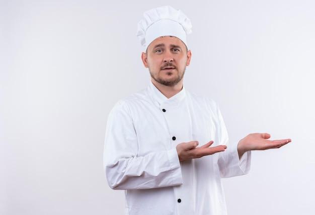 Impressionato giovane bel cuoco in uniforme da chef che punta con le mani sul lato isolato sul muro bianco