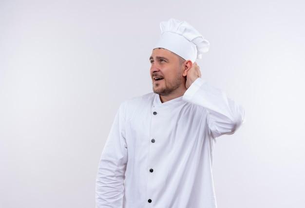Impressionato giovane bel cuoco in uniforme da chef mettendo la mano dietro la testa e guardando il lato isolato sul muro bianco white