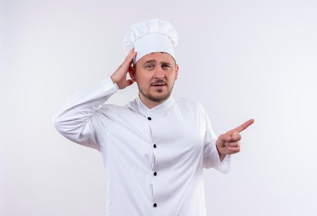 Impressionato giovane e bello cuoco in uniforme da chef mettendo la mano sulla testa e indicando il lato destro isolato sul muro bianco