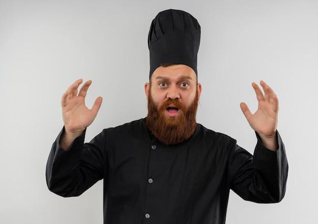 Impressionato giovane bel cuoco in uniforme da chef alzando le mani isolato su muro bianco