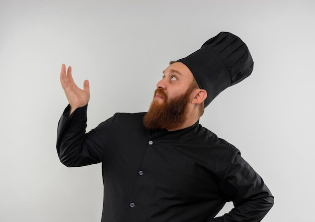 Impressionato giovane bel cuoco in uniforme da chef che mostra la mano vuota e alzando lo sguardo isolato sul muro bianco