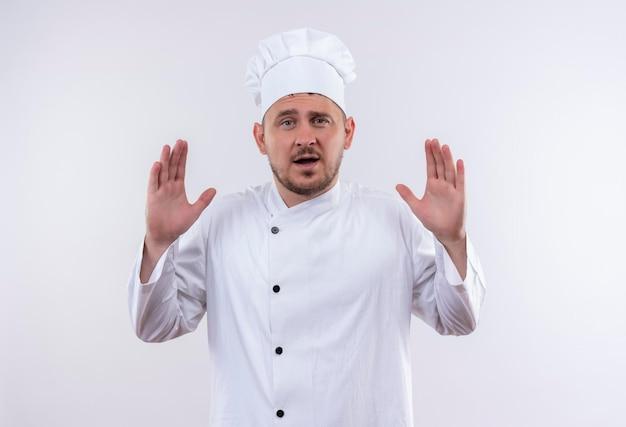 Impressionato giovane bel cuoco in uniforme da chef che mostra le mani vuote isolate sul muro bianco