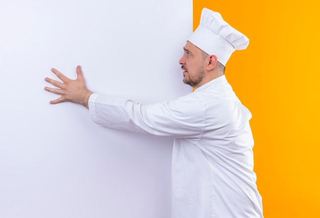 Impressionato giovane bel cuoco in uniforme da chef in piedi di fronte al muro bianco mettendoci sopra la mano guardando il lato isolato sul muro arancione