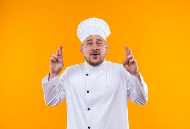 オレンジ色の壁に分離された交差した指のジェスチャーをしているシェフの制服を着た若いハンサムな料理人に感銘