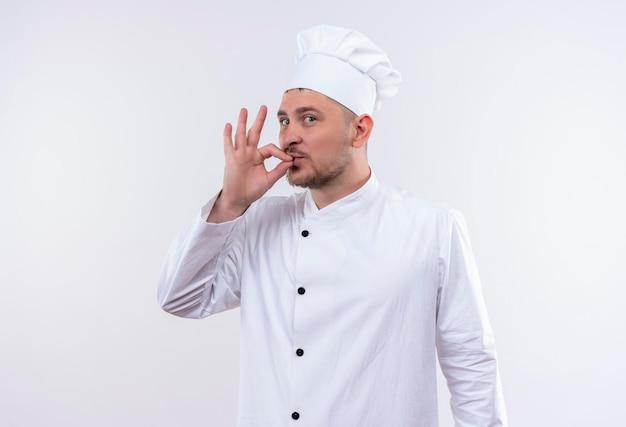 白い壁に分離されたおいしい看板をしているシェフの制服を着た若いハンサムな料理人に感銘