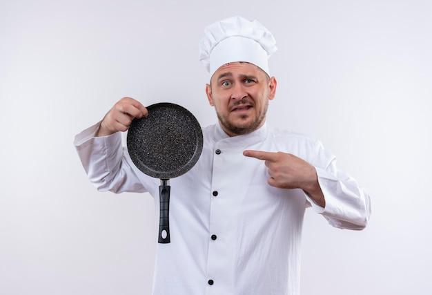 シェフの制服を着た若いハンサムな料理人が、白い壁に分離されたフライパンを押しながら指している