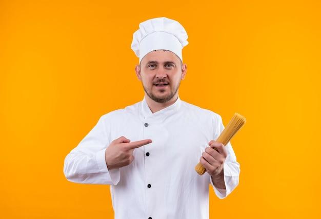 オレンジ色の壁に分離されたスパゲッティ パスタを保持し、指差すシェフの制服を着た若いハンサムな料理人に感銘
