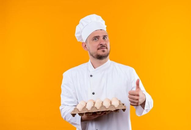 オレンジ色の壁に孤立した親指を現して卵のカートンを保持しているシェフの制服を着た若いハンサムな料理人に感銘