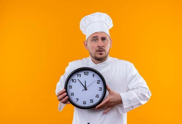 オレンジ色の壁に分離された時計を保持しているシェフの制服を着た若いハンサムな料理人に感銘
