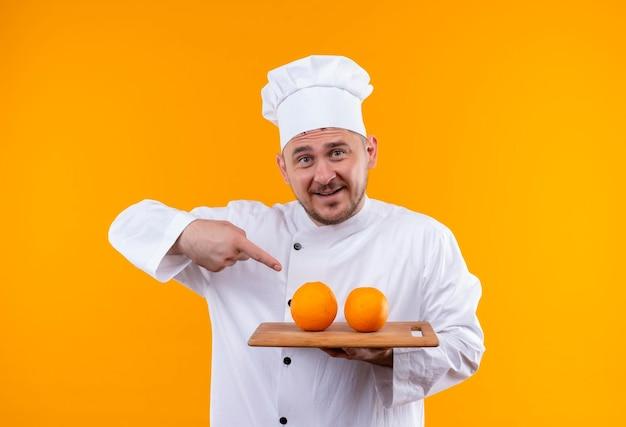 オレンジ色の壁に分離されたそれらを指し示すオレンジ色のまな板を保持しているシェフの制服を着た若いハンサムな料理人に感銘を受けた