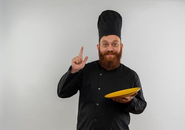 빈 접시를 들고 복사 공간이 흰 벽에 고립 된 손가락을 올리는 요리사 유니폼에 감동 된 젊은 잘 생긴 요리사