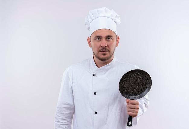 흰 벽에 고립 된 프라이팬을 들고 요리사 유니폼에 감동 된 젊은 잘 생긴 요리사
