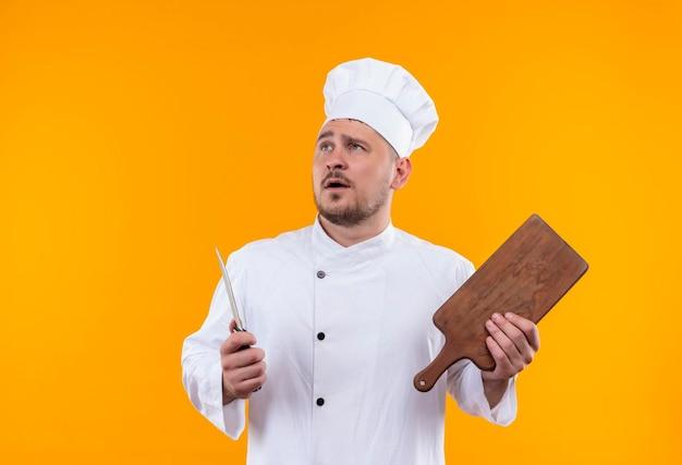オレンジ色の壁に孤立した見上げるナイフとまな板を保持しているシェフの制服を着た若いハンサムな料理人に感銘
