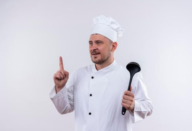 鍋を持ち、白い壁に孤立した側を見て指を上げるシェフの制服を着た若いハンサムな料理人に感銘