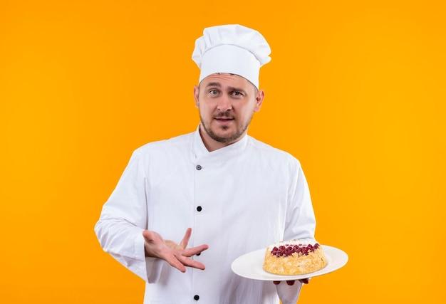 Впечатленный молодой красивый повар в униформе шеф-повара держит тарелку торта и указывает на нее, изолированной на оранжевой стене