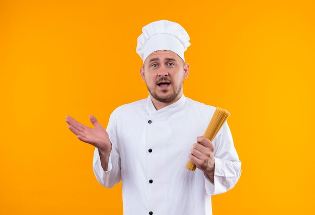 スパゲッティ パスタを保持し、オレンジ色の壁に孤立した空の手を示すシェフの制服を着た印象的な若いハンサムな料理人