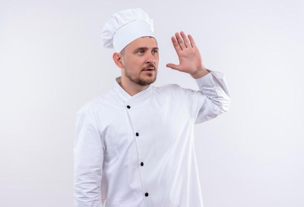 シェフの制服を着た若いハンサムな料理人が白い壁に上げられた手を見て側を見ている