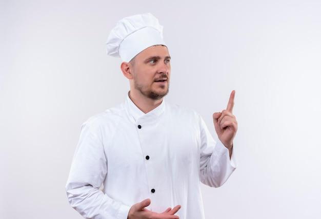 흰 벽에 고립 된 오른쪽에서 찾고 가리키는 요리사 유니폼에 감동 된 젊은 잘 생긴 요리사