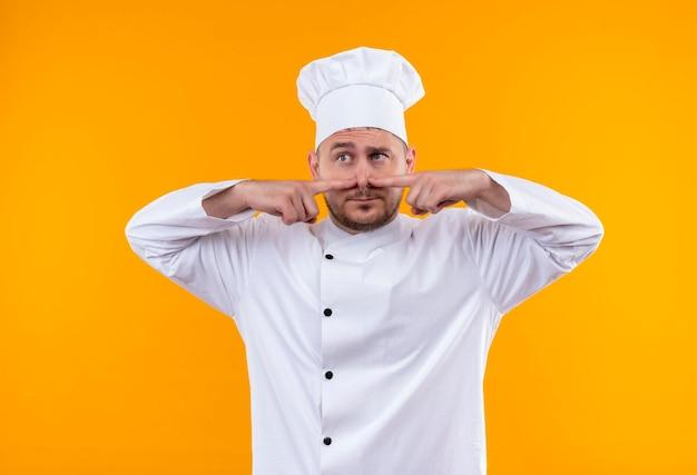 オレンジ色の壁に隔離された側を見て、鼻に指を当ててシェフの制服を着た若いハンサムな料理人に感銘