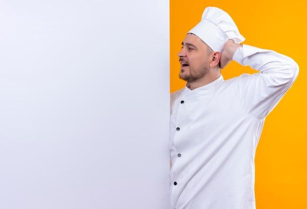 白い壁の後ろに立つシェフの制服を着た若いハンサムな料理人が、コピースペースのあるオレンジ色の壁に手でそれを指している