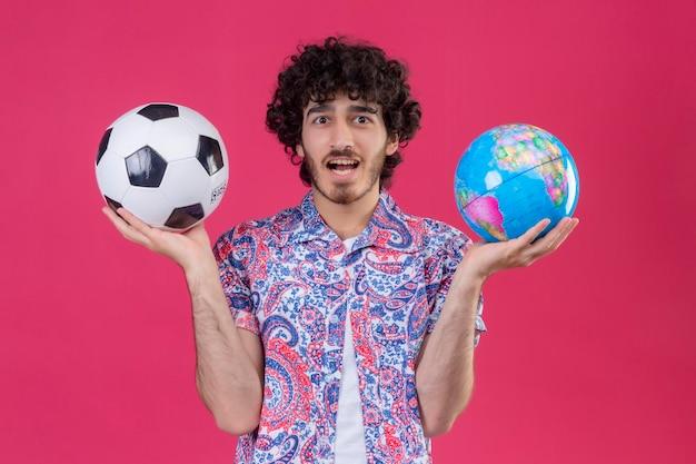 Впечатленный молодой красивый кудрявый путешественник, держащий глобус и футбольный мяч на изолированном розовом пространстве