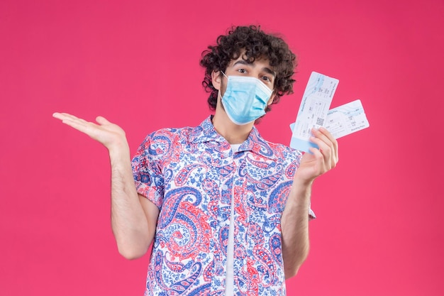 Impressed young handsome curly traveler man wearing medical mask holding airplane tickets showing empty hand on isolated pink space
