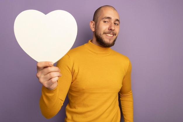 Impressed young handsome guy holding heart shape box isolated on purple