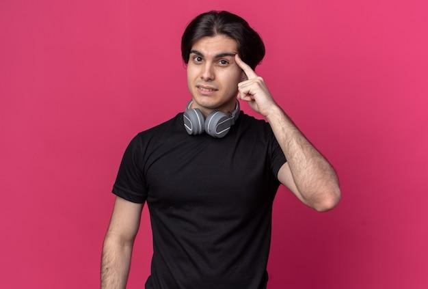 분홍색 벽에 고립 된 사원에 손가락을 넣어 목 주위에 검은 색 티셔츠와 헤드폰을 착용하는 감동 된 젊은 잘 생긴 남자
