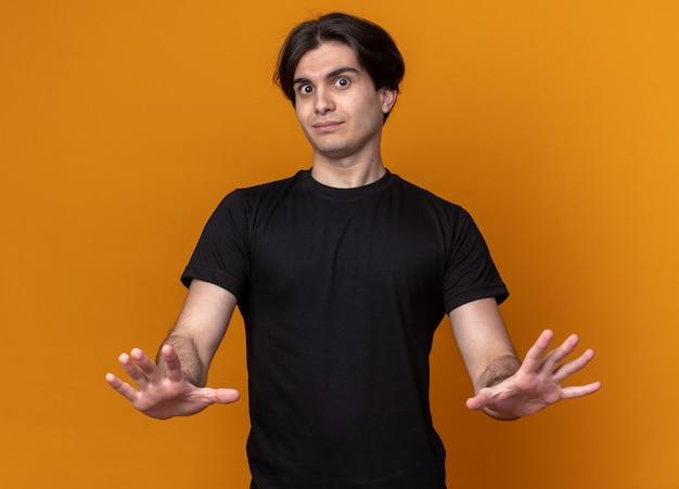 Впечатленный молодой красивый парень в черной футболке, показывающий жест стоп, изолированный на оранжевой стене