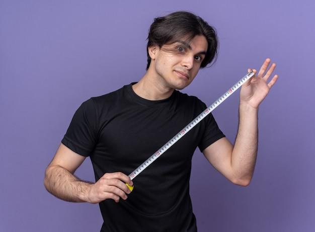 Впечатленный молодой красивый парень в черной футболке, протягивающий рулетку, изолированную на фиолетовой стене
