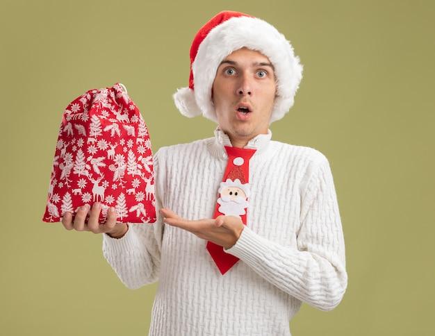 クリスマスの帽子とサンタクロースのネクタイを身に着けている感動の若いハンサムな男は、オリーブグリーンの背景に分離されたカメラを見てクリスマス袋を手で指しています